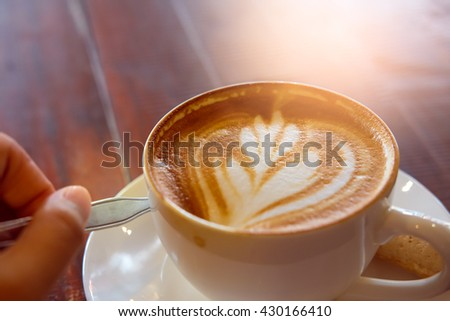 Holding a cup of fresh hot coffee on white plate  on wooden background with abstract light,selective focus - stock photo