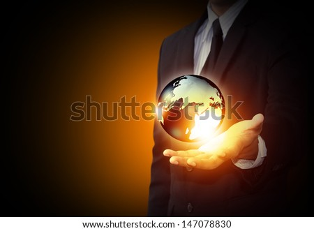 Holding a glowing earth globe in hand - stock photo