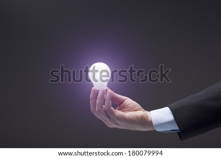 Holding a Glowing Light Bulb - stock photo