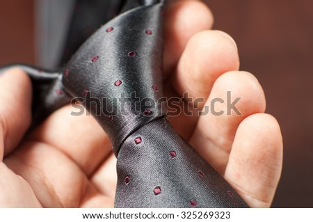 Holding a grey tie.