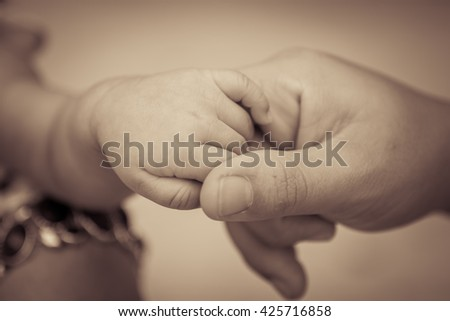 holding a hand of the newborn child ,mono tone, sepia tone