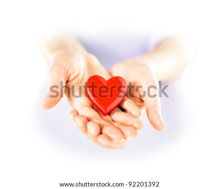 Holding a heart in cupped hands. Love and health care concept