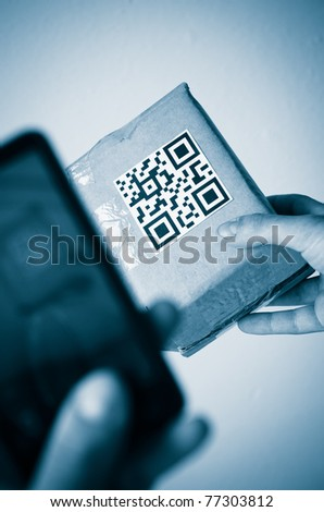 holding a  qr code with smartphone - stock photo