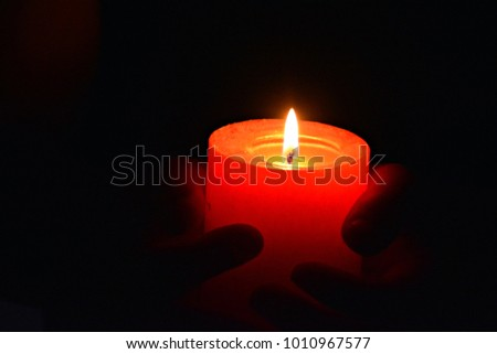 holding a red candle in the dark close up