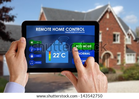 Holding a smart energy controller or remote home control online home automation system on a digital tablet. All screen graphics made up. - stock photo