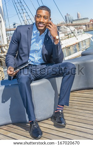 Holding a tablet computer on his lap, a young black businessman is sitting on a deck and smilingly talking on the phone. The background is a harbor. / Working Outside - stock photo