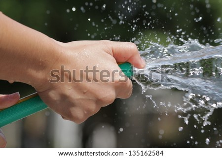 Holding a water rubber hose tube. Watering. hose down. - stock photo