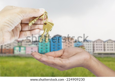 Holding and giving brass keys to anyone - stock photo