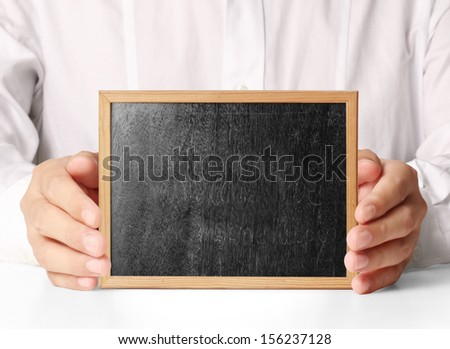 holding blank chalkboard in hand - stock photo