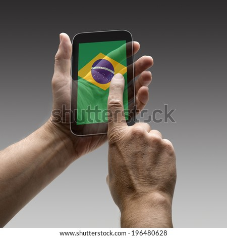Holding Brazil flag screen smart phone. There is a route for hand and finger.  - stock photo