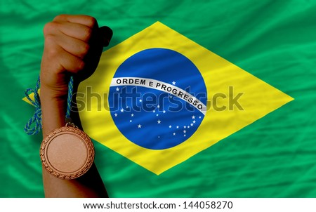 Holding bronze medal for sport and national flag of brazil
