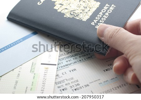 Holding Canada passport with boarding pass