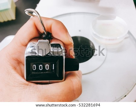 Holding counter on laboratory background (microscope and bio-plate)
