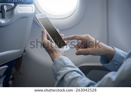 holding digital mobile phone at airplane - stock photo