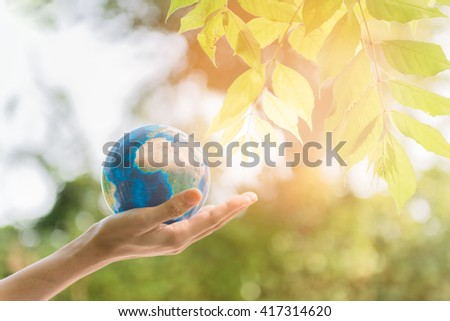 Holding earth planet in the hand with tree and against green spring background.  Corporate Social Responsibility or CSR concept. Elements of this image furnished by NASA - stock photo