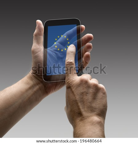 Holding Europe flag screen smart phone. There is a route for hand and finger.  - stock photo