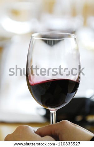 Holding glass of red wine, cropped