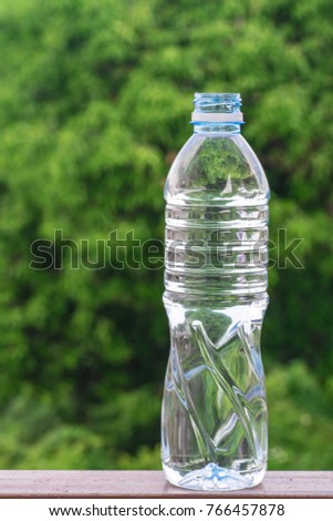Holding glass water tree blurry background.Using wallpaper for package or product, refreshing image and copy space