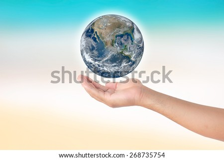 holding globe in hands blurred background.Elements of this image furnished by NASA - stock photo
