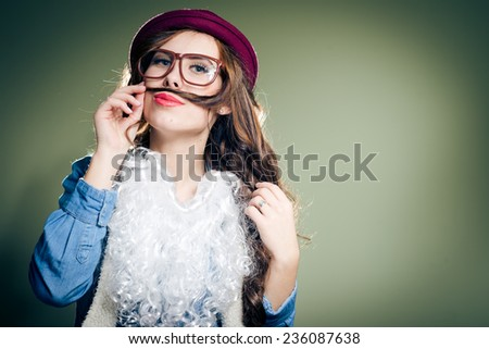 holding hair as mustache funny hipster beautiful young lady in super size eyeglasses wearing xmas santa hat and faux beard over olive copy space background - stock photo