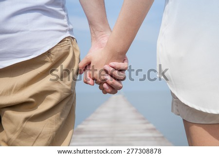 holding hand by the beach