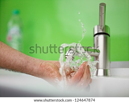 holding hand under sparkling fresh water out of the faucet - stock photo