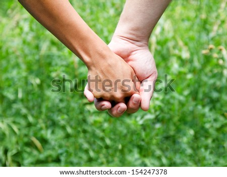 Holding hands against a green background - stock photo