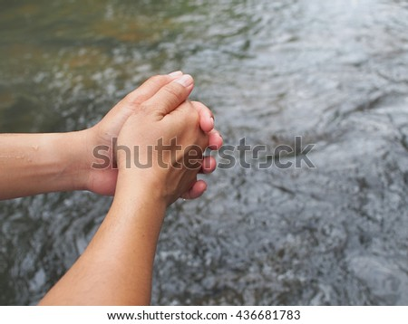 holding hands and water background, relaxing time with part of water fall from the national park.