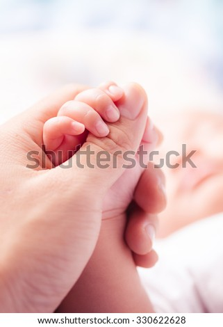Holding Hands. hand the sleeping baby in the hand of parent close-up