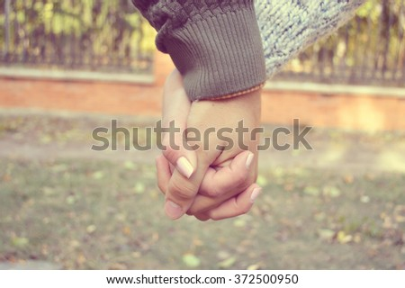 Holding hands.Lovers couple holding hands in a forest (summer/spring).Hand in hand - stock photo