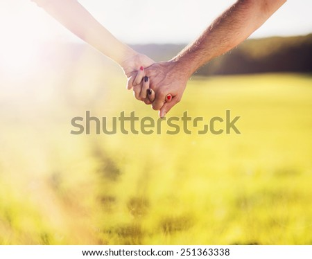 Holding hands of happy young couple having fun outside in a park - stock photo