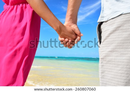 Holding hands romantic newlyweds couple on beach. Closeup of male and female hands with a sunny blue beach background as honeymoon concept or happy relationship during travel summer holidays. - stock photo