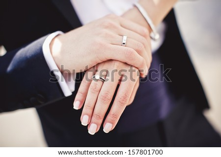 Holding hands with wedding rings - stock photo