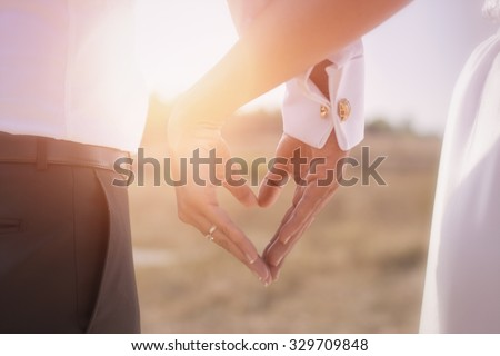 Holding Hands with wedding rings on the background of sunlight - stock photo
