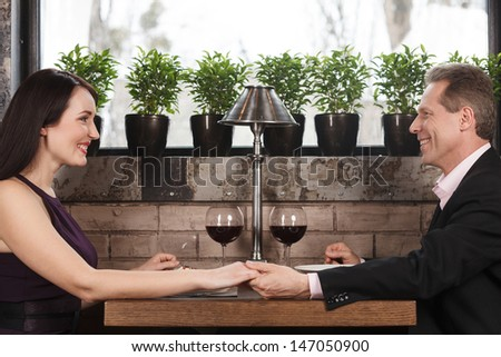 Holding her hand. Happy mature couple sitting at the restaurant and holding hands - stock photo