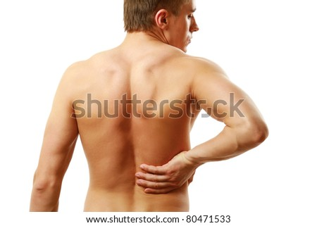 Holding his back in pain. - stock photo