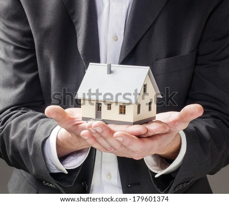 holding home for selling and buying strategy - stock photo