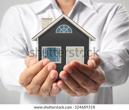 holding house representing home ownership and the Real Estate busines