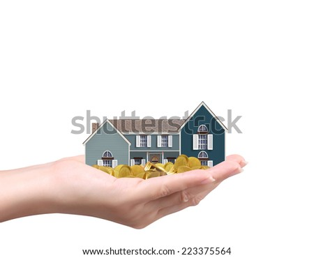 holding house representing home ownership and the Real Estate business holding house and coins