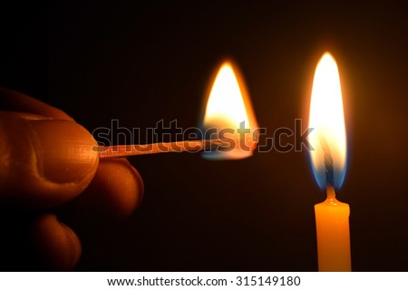 Holding Matches and candle fire on black background - stock photo