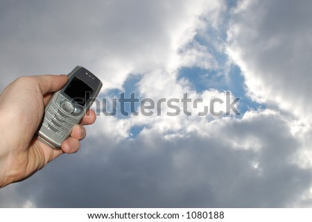 holding mobile phone on sky background