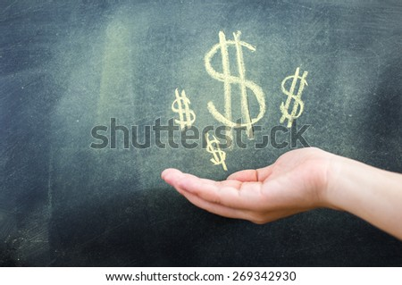 holding money on blackboard - stock photo