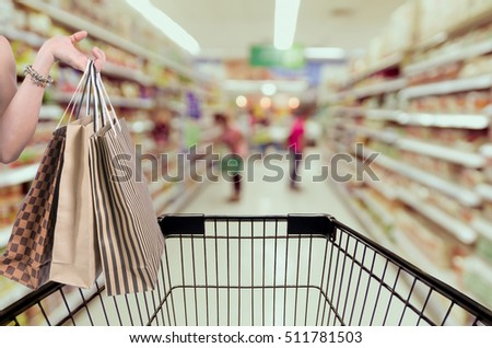 Holding shoping bags by hand on Supermarket with Abstract blurred photo of store with trolley in department store bokeh background