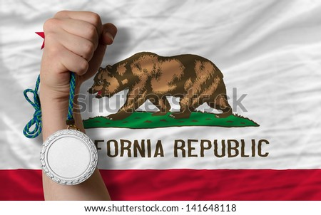 Holding silver medal for sport and flag of us state of california - stock photo