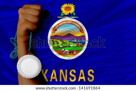 Holding silver medal for sport and flag of us state of kansas - stock photo