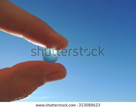 Holding small glass sphere at clear blue sky background