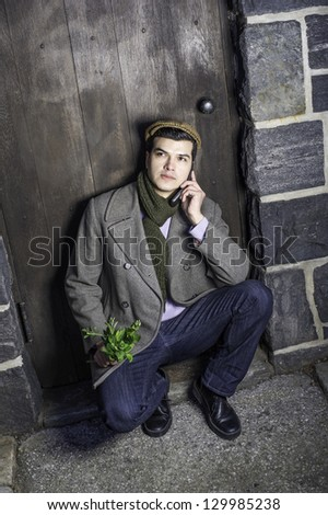 Holding small green plants and talking on the phone, a young guy is waiting on the door way.