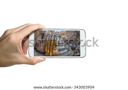 Holding smart phone for capture, Take a photo of Sukhothai Historical Park , Thailand. - stock photo