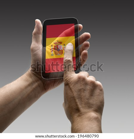 Holding Spain flag screen smart phone. There is a route for hand and finger.  - stock photo