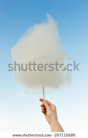 Holding Sweet Cotton Candy on Stick on Blue Sky background - stock photo